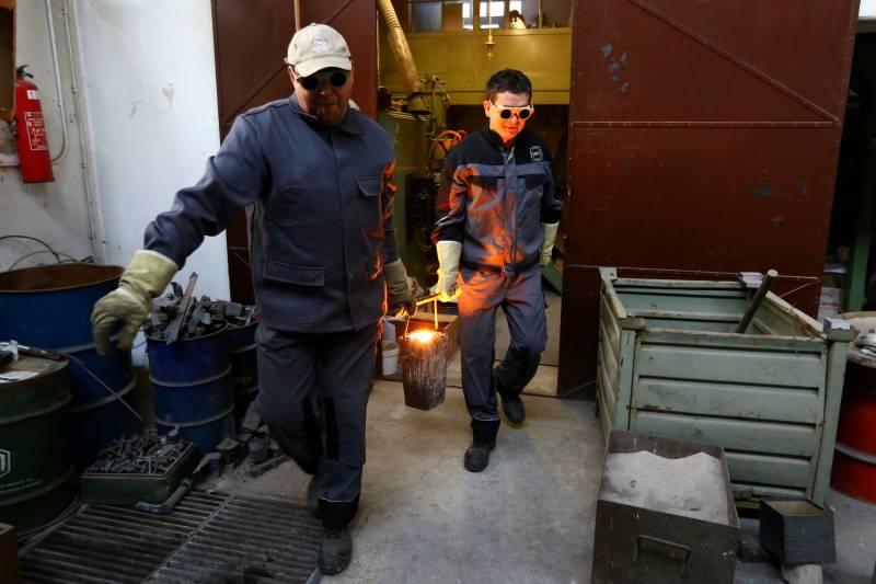 Jaka Burja (spredaj) s sodelavcem in 1200 stopinj Celzija vročim kosom jekla. (foto: osebni arhiv JB)