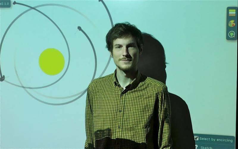 Bor Gregorčič pred interaktivno tablo, ki sproti prikazuje pripravljeno animacijo Kepplerjevih zakonov. (foto: osebni arhiv BG)