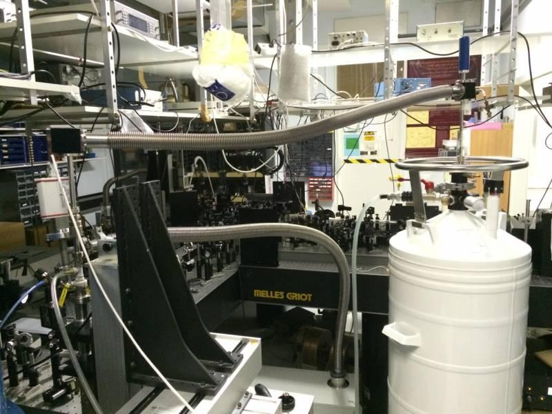 Merjenje preklopov v optičnem laboratoriju - posoda s tekočim helijem na desni dovaja helij za hlajenje do namiznega kriostata z vzorcem. Na mizi so nosilci z lečami, zrcali in optičnimi komponentami, ki spreminjajo dovedeni laserski snop.